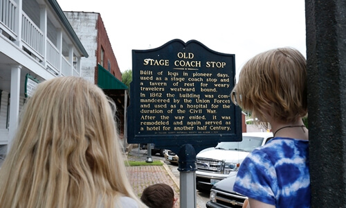 Family reading historic marker outside Waynesville's Old Stagecoach Stop