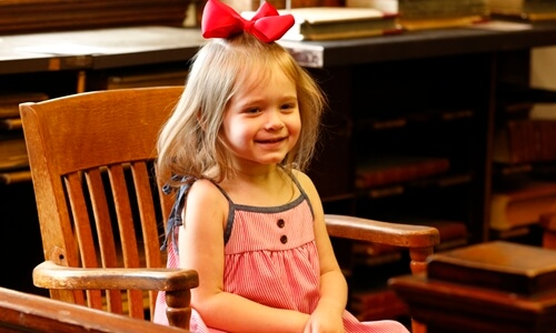 Female child sits in vintage juror's seat in vintage Ozarks courtroom, Waynesville, Missouri