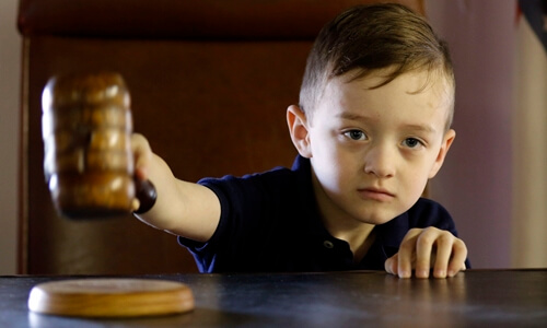 Child with antique gavel in vintage courtroom at Waynesville, Missouri