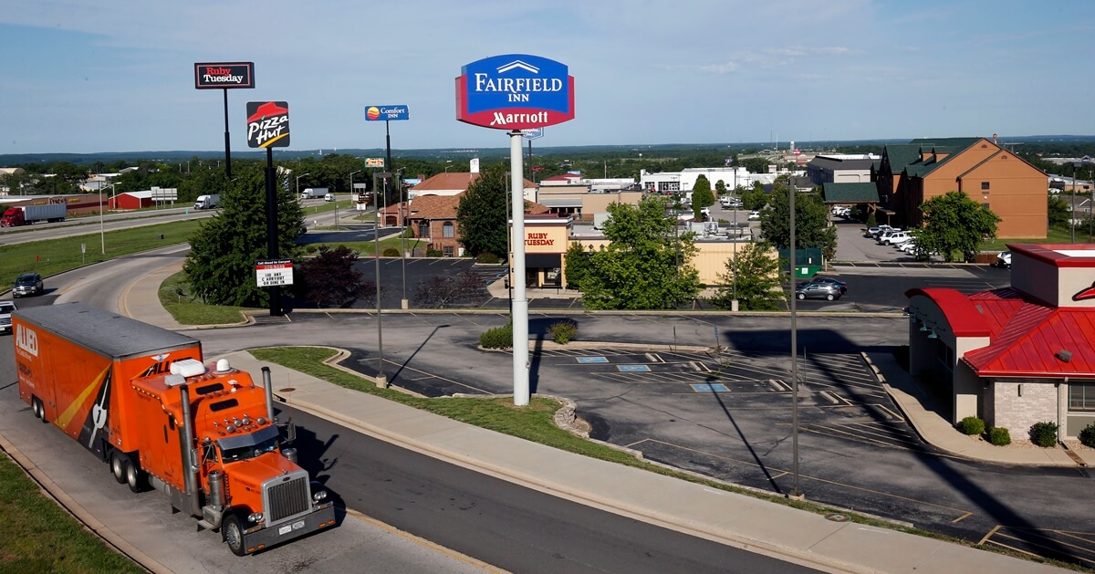 Semi-Truck & Trailer on Saint Robert Boulevard with lodging and hotel signs in background
